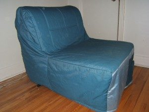 Here is a futon chair covered with a royal blue cover.